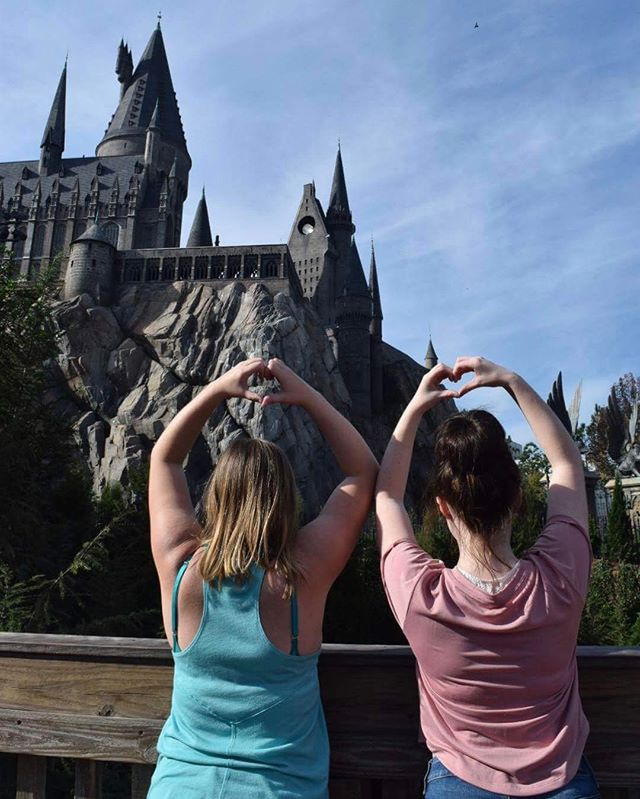 Two girls posing in front of Hogwarts Castle in Universal Studios Orlando