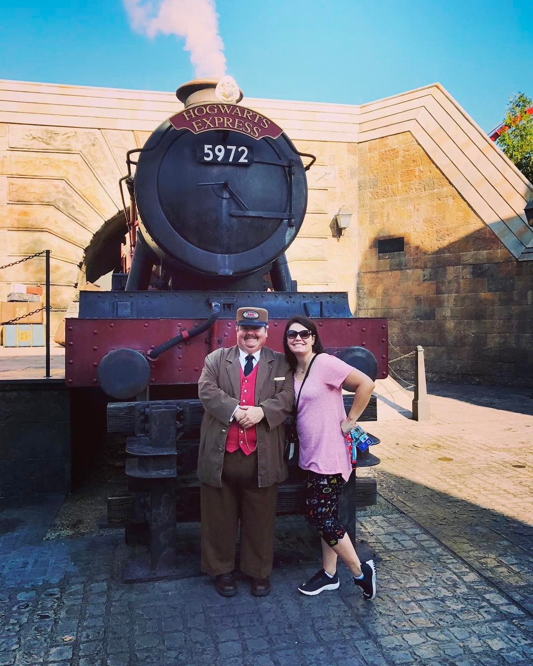 A woman poses in front of the Hogwarts Express