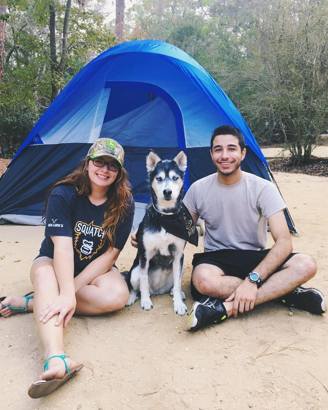 A man, woman, and dog pose outside their tent
