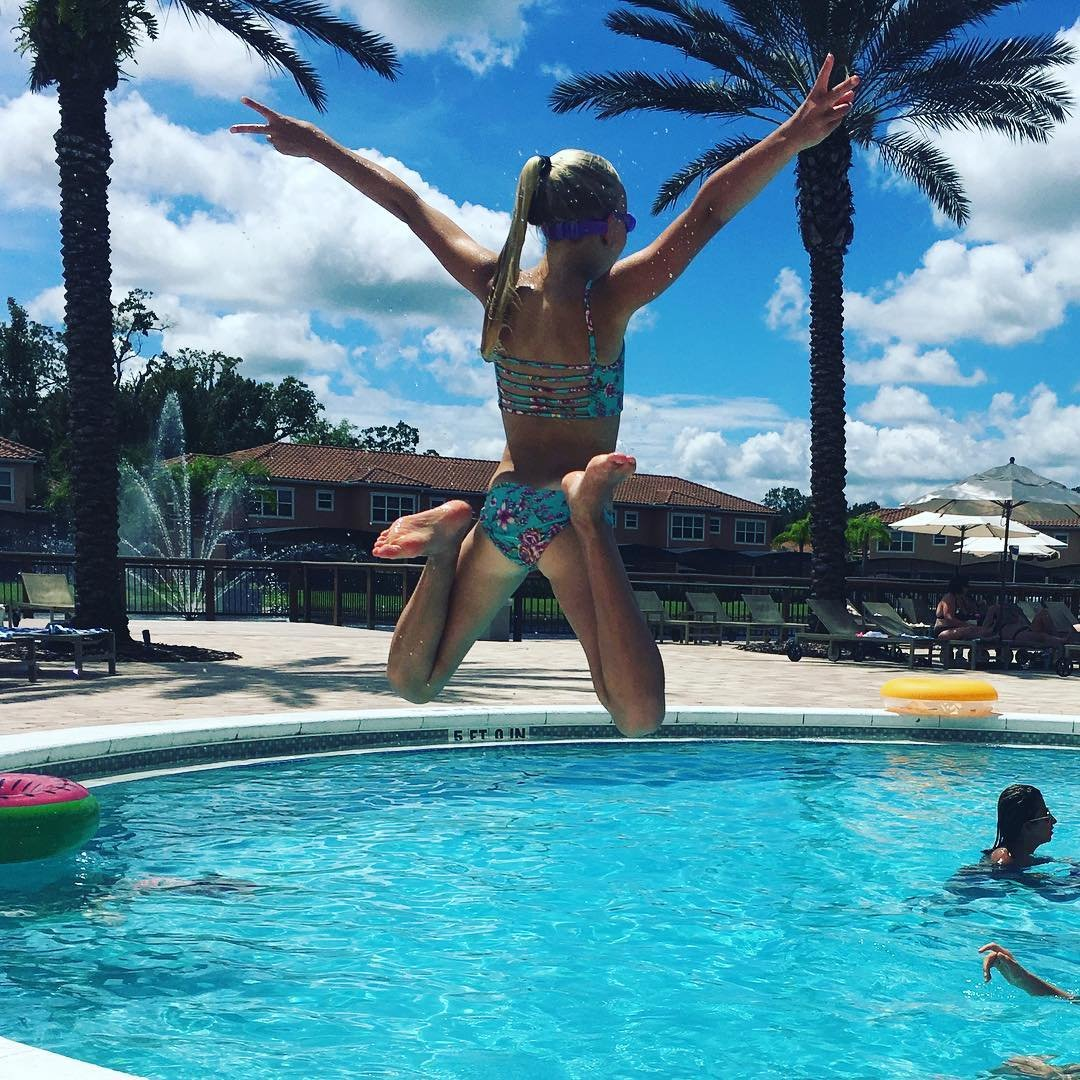 A girl jumps into a pool in Kissimmee