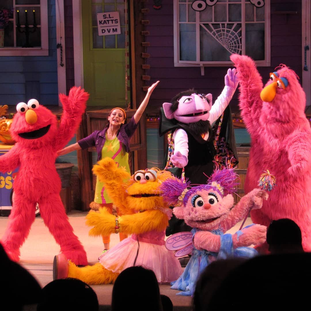 Characters from Sesame Street dance on stage