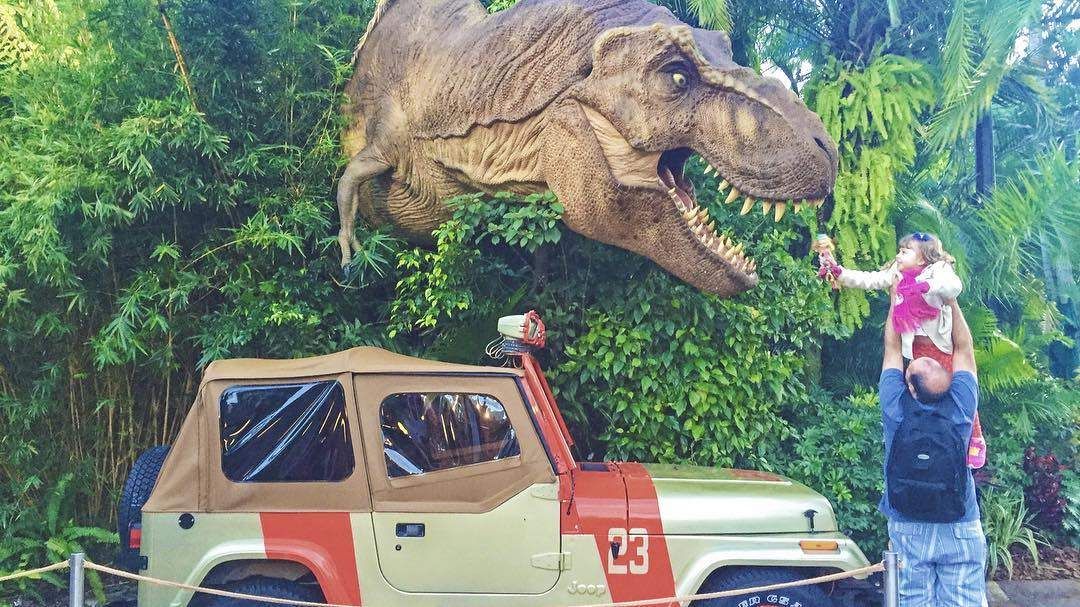 A father and daughter pose next to a T-Rex in Universal Studios