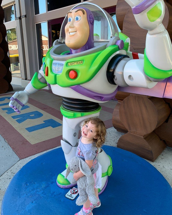 A child hugs Buzz Lightyear