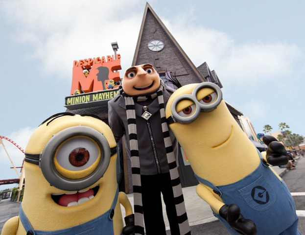 Gru and two yellow minions on the set of the Despicable Me Minion Mayhem ride and in front of Gru's brown house.