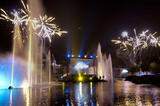 A large fountain at night with fireworks going off in the background and a screen with the Universal Studios logo.