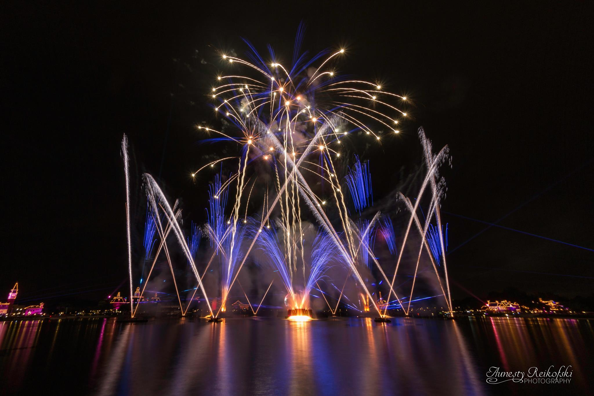 A lake at night with fountain going high into the air and multiple blue and white fireworks going off in the sky.