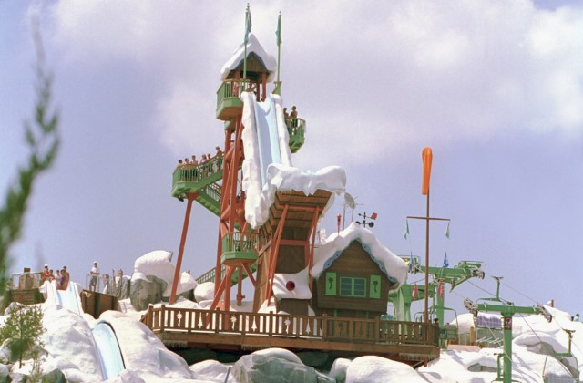 A brown house with a tall tower and slide covered in fake snow at Disney's Blizzard Beach waterpark on a sunny day.