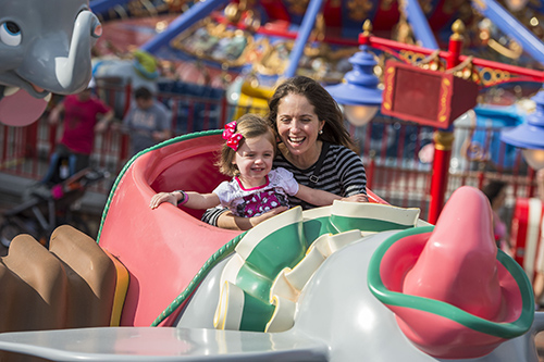 A mother and daughter inside a cart on the Dumbo ride in Kissimmee, Florida on a sunny day.