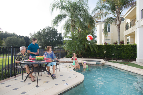 Three adults sitting at a table on a pool deck watching three children playing with a beach ball in the water.