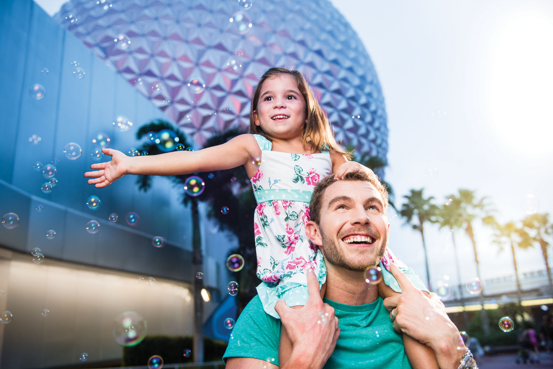 A father walks through Epcot with his daughter on his shoulders