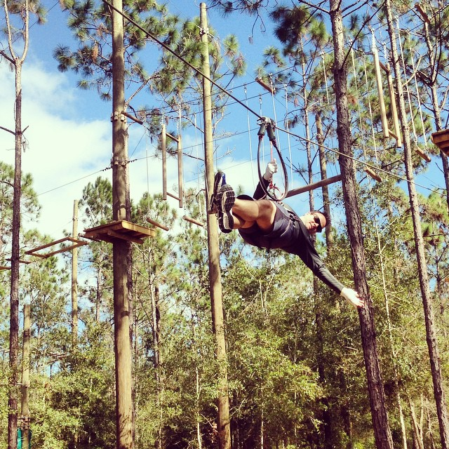 A man zip lining through the woods while waving at Orlando Tree Trek in Kissimmee, Florida.