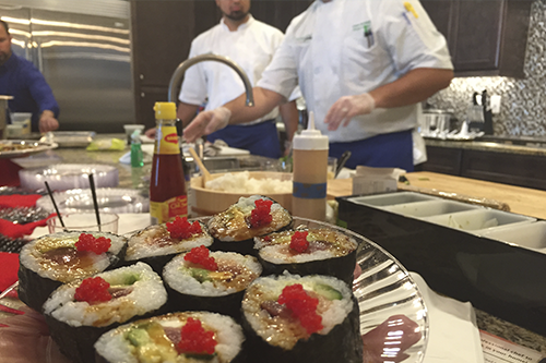 Chefs prepare an assortment of sushi for diners in a restaurant.