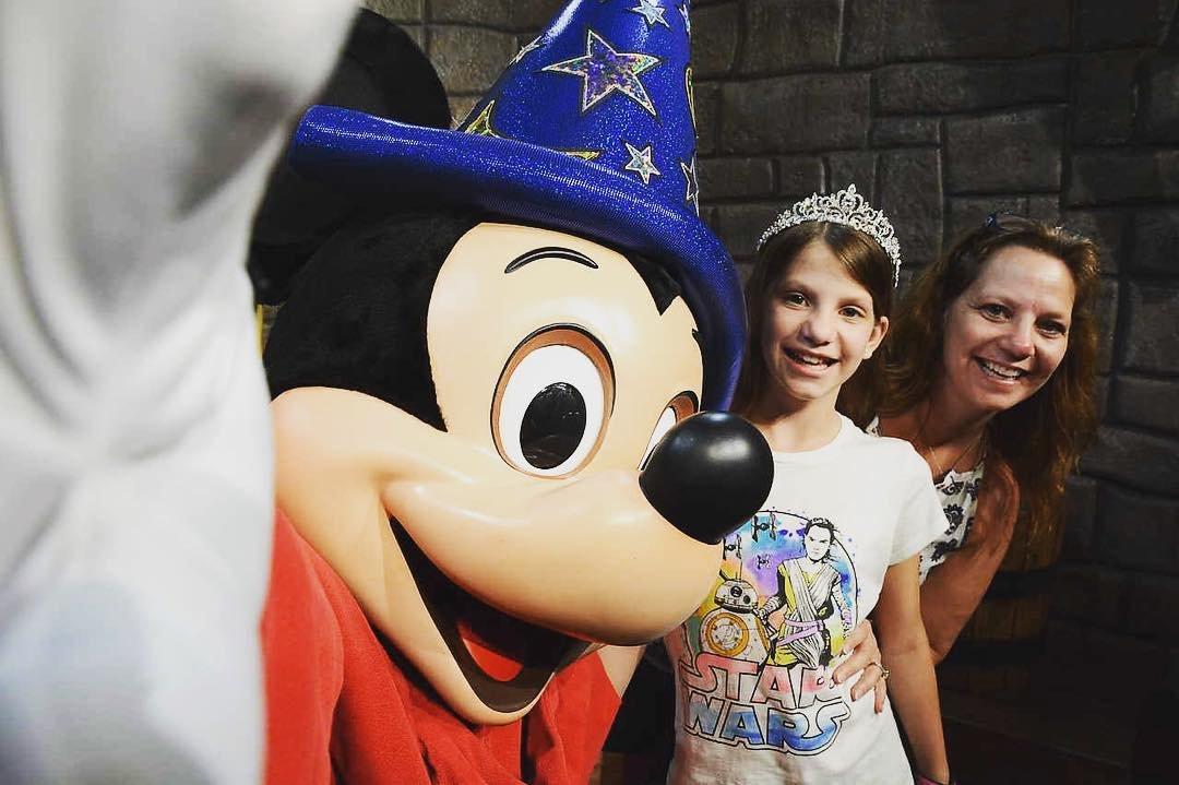 A woman and her daughter pose with Mickey Mouse