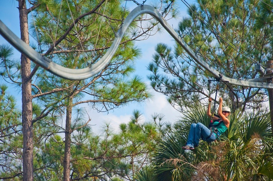 A woman ziplining through tall trees in a twisted line in Kissimmee, Florida on a sunny day.
