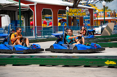 Father and daughter in blue go karts going around a turn on the track in Kissimmee, Florida.