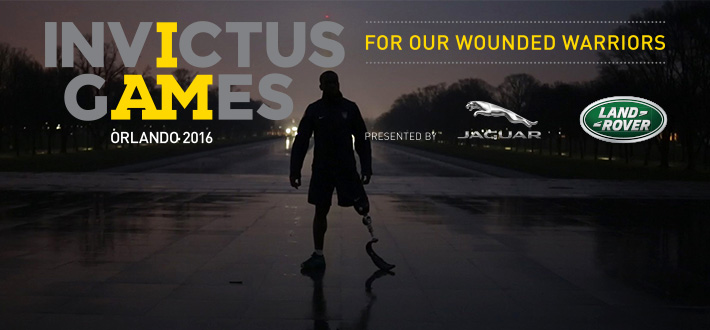 A man with one artificial leg standing on a street at night advertising for Invictus Games Orlando 2016.