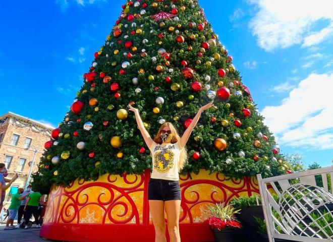 A lady raises her hands underneath a Christmas Tree at Universal Studios
