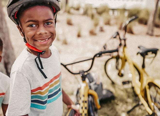 A boy stands with a yellow bike in Celebration, Florida.