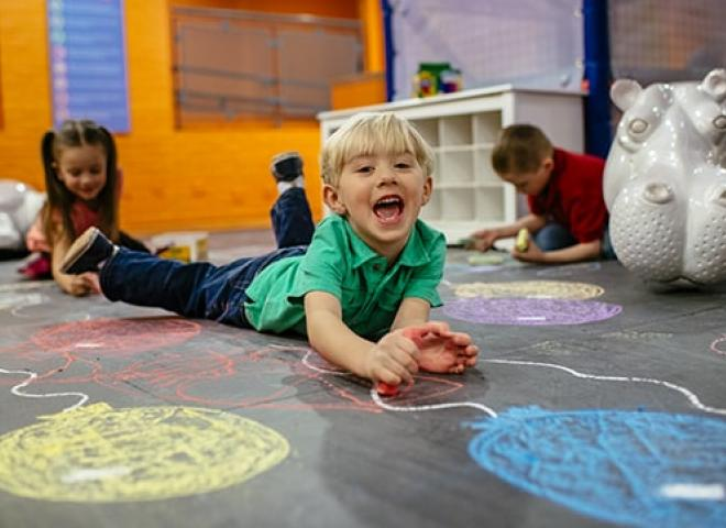 Boy down floor drawing with chalk