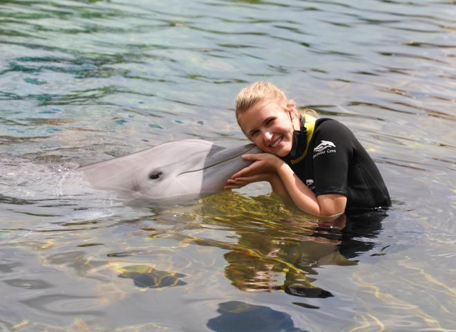 A woman kisses a dolphin at Discovery Cove in Kissimmee