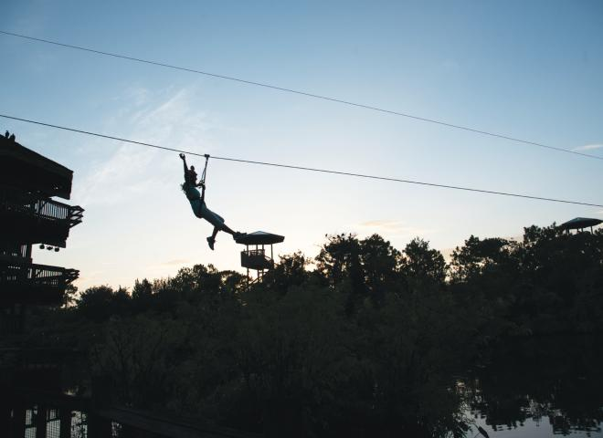 A guest rides the zip line at Gatorland
