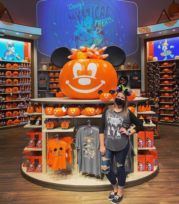 A woman stands in front of a clothing display at Disney World