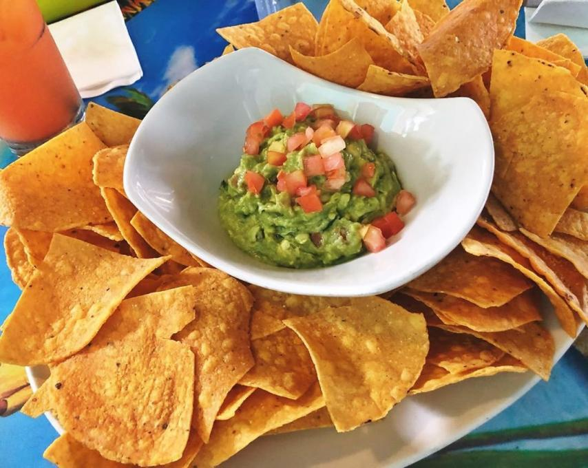 A plate of nacho chips with guacamole.