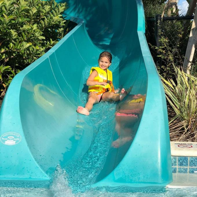 A child slides down a water slide