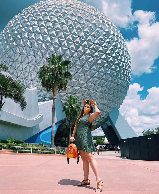 A lady stands outside Spaceship Earth at EPCOT
