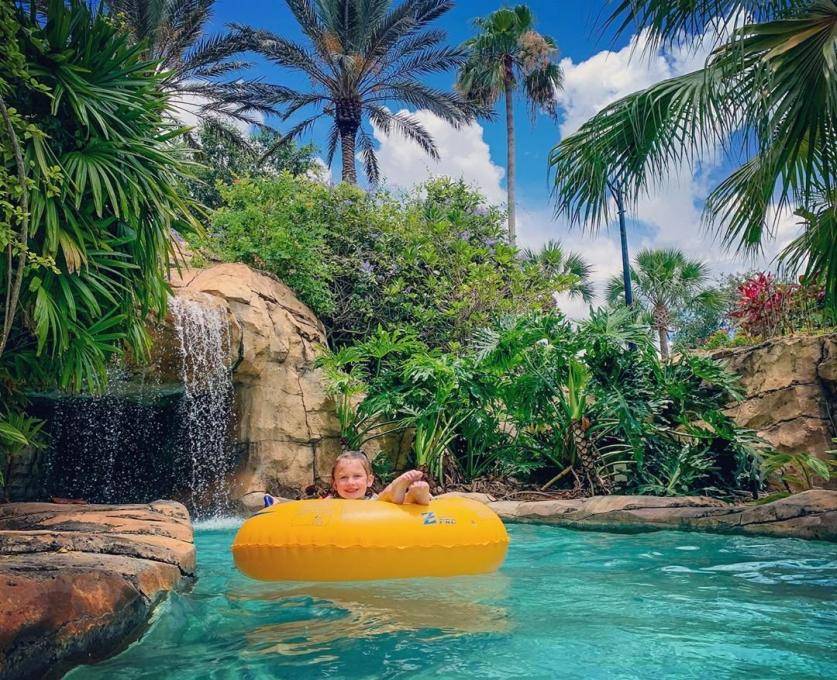 A little girl rides the lazy river at Reunion Resort & Golf Club