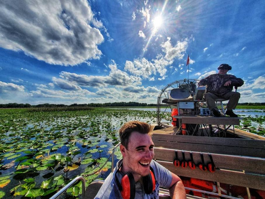 A man smiles while riding an airboat in Kissimmee, Florida