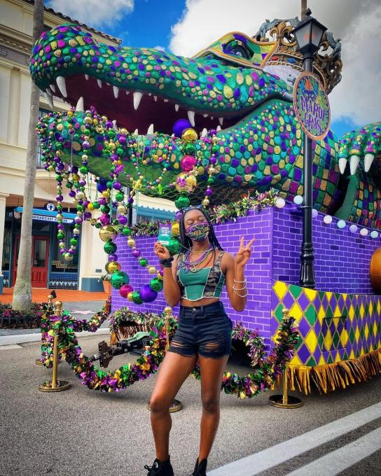 A lady poses in front of a float during Mardi Gras
