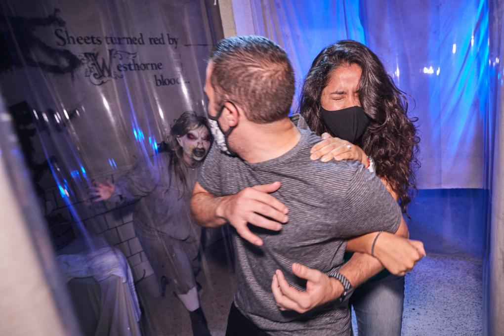 A couple is scared at a haunted house at Universal Orlando