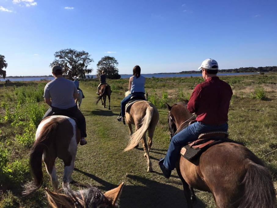 People ride horses at the Lazy H Ranch