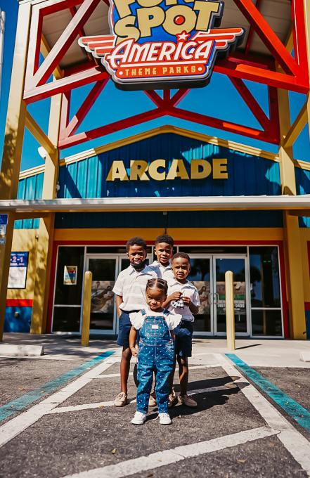 Four children stand in front of the entrance to Fun Spot Kissimmee.