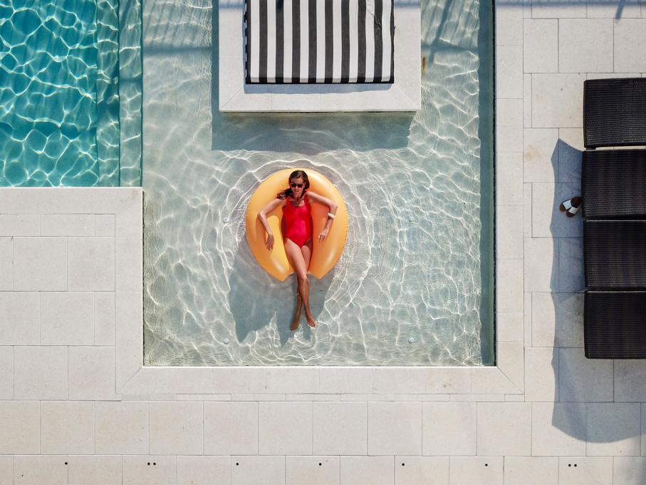 A woman relaxes in the pool at her vacation home