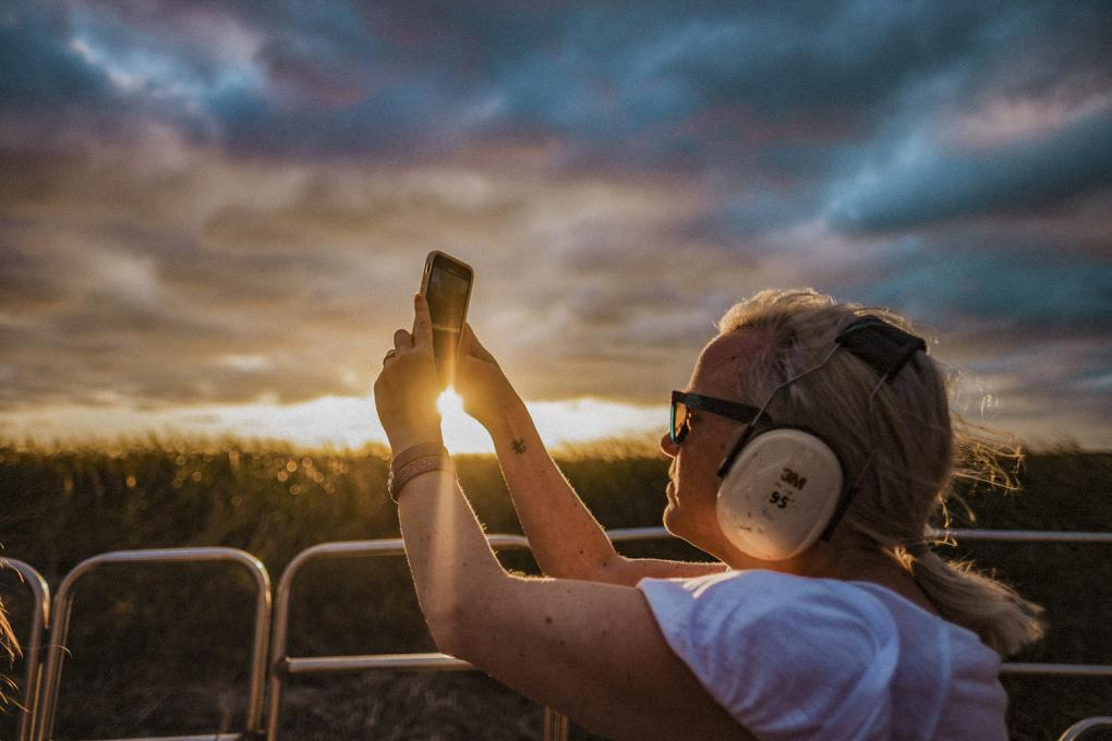A lady takes a photo on an airboat ride at Wild Florida