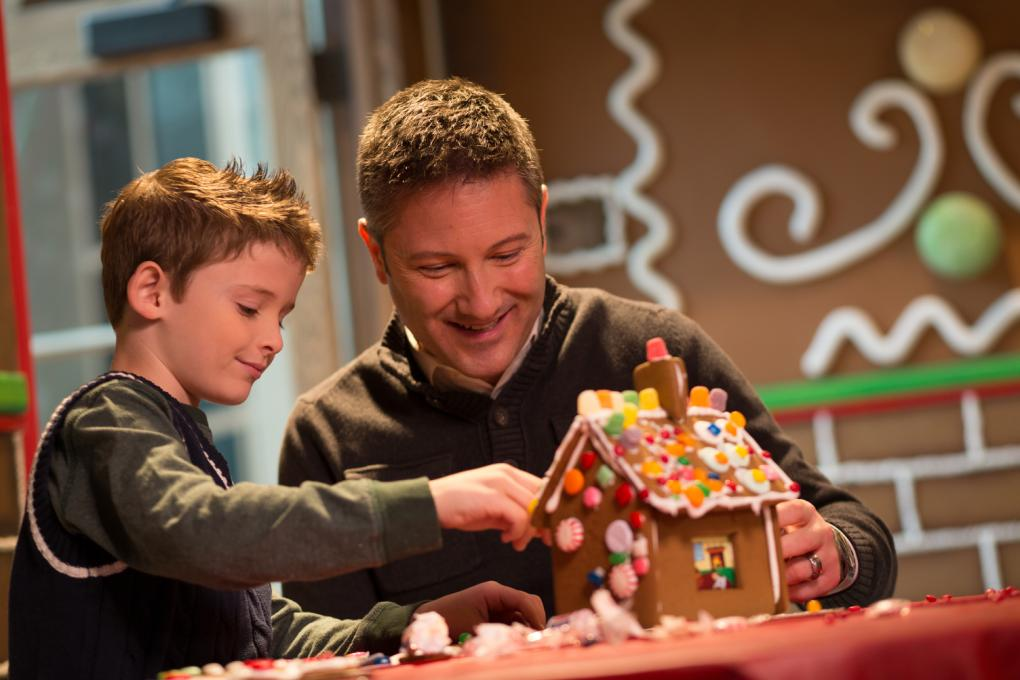 A father and son decorate a gingerbread house together