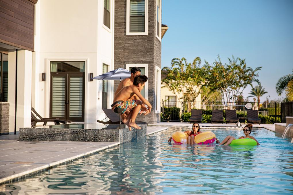 Kids jump in a pool at a vacation home