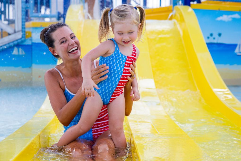 A mother and child slide down a waterslide together