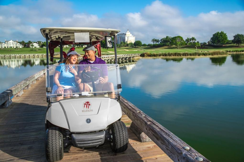 A man and woman drive in a golf kart in Kissimmee