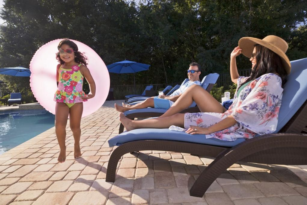 A man and woman relax by the pool while a young girl walks by them