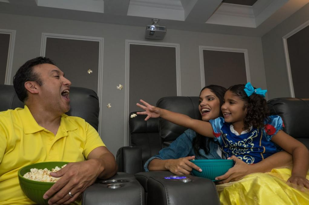 A family hangs out and eats popcorn in a Kissimmee vacation home