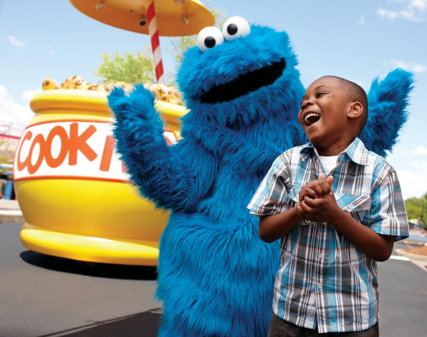 A child and cookie monster take a photo together
