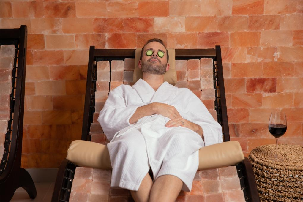 A man in a robe with cucumbers over his eyes at Relâche Spa at Gaylord Palms Resort & Convention Center