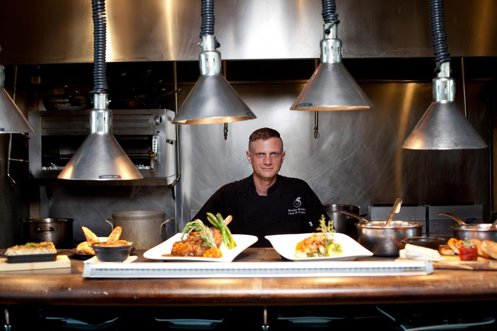 A chef looks over a meal prepared in his restaurant