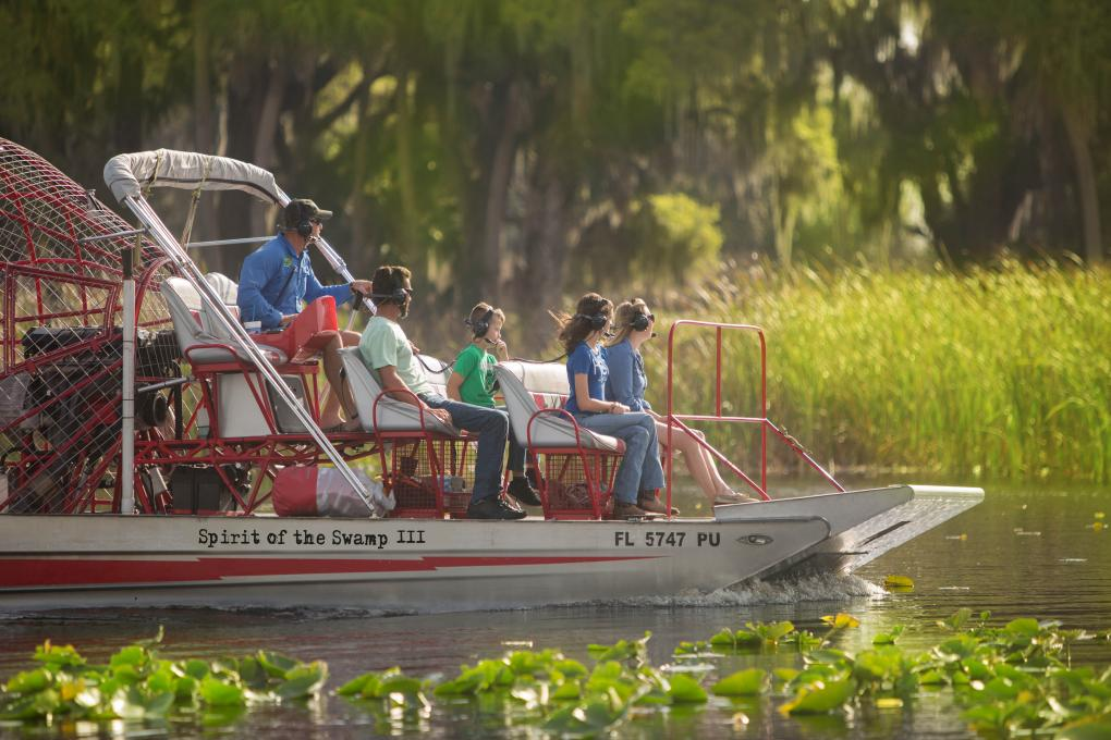 Visitors to Kissimmee, Florida ride a boat at Spirit of the Swamps