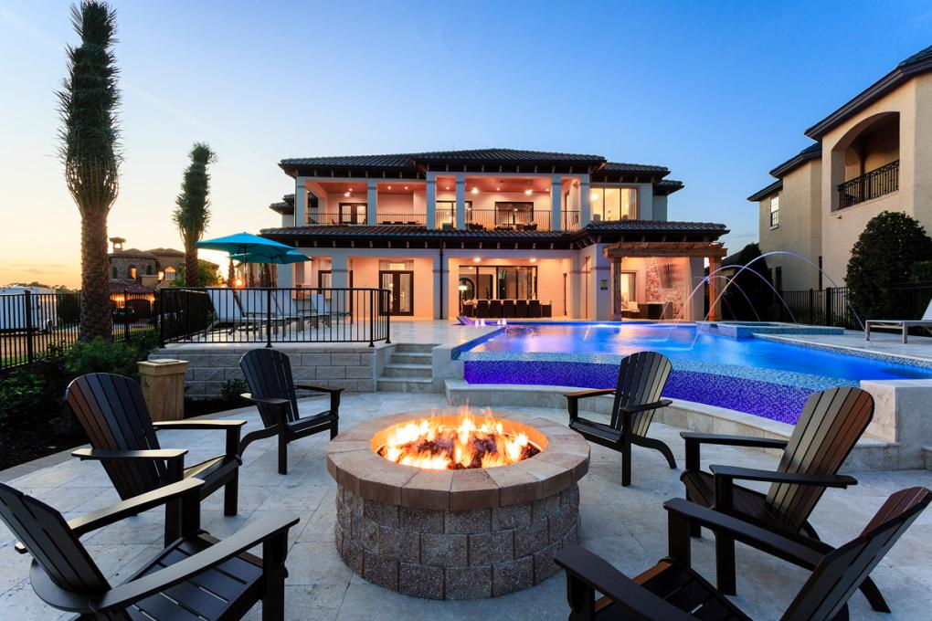 A two story Mediterranean style vacation home sits in the back ground, with a pool, chairs and fire pit in the foreground at dusk.