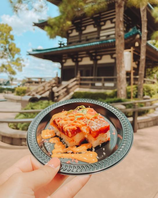 hand holding a plate of sushi in front of a pagoda