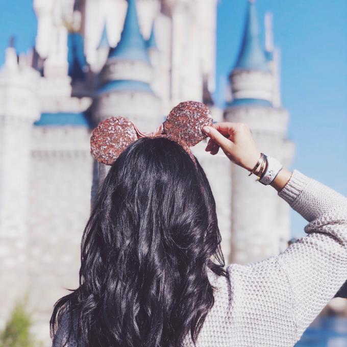 Woman with Mickey Mouse ears stands in front of castle.